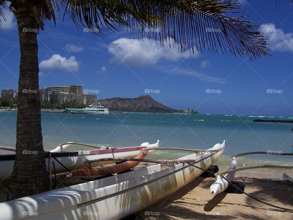 Outrigger Canoe & Diamond Head. An outrigger canoe on a beach in Waikiki with Diamond Head in the distance.