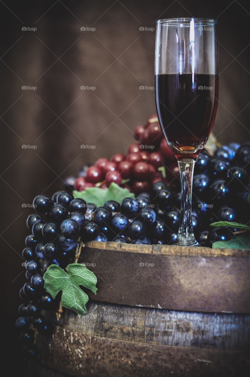 Wine and grapes on rustic wooden barrel