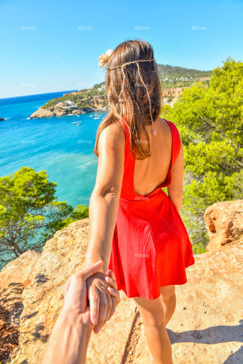 Woman holding man's hand on cliff
