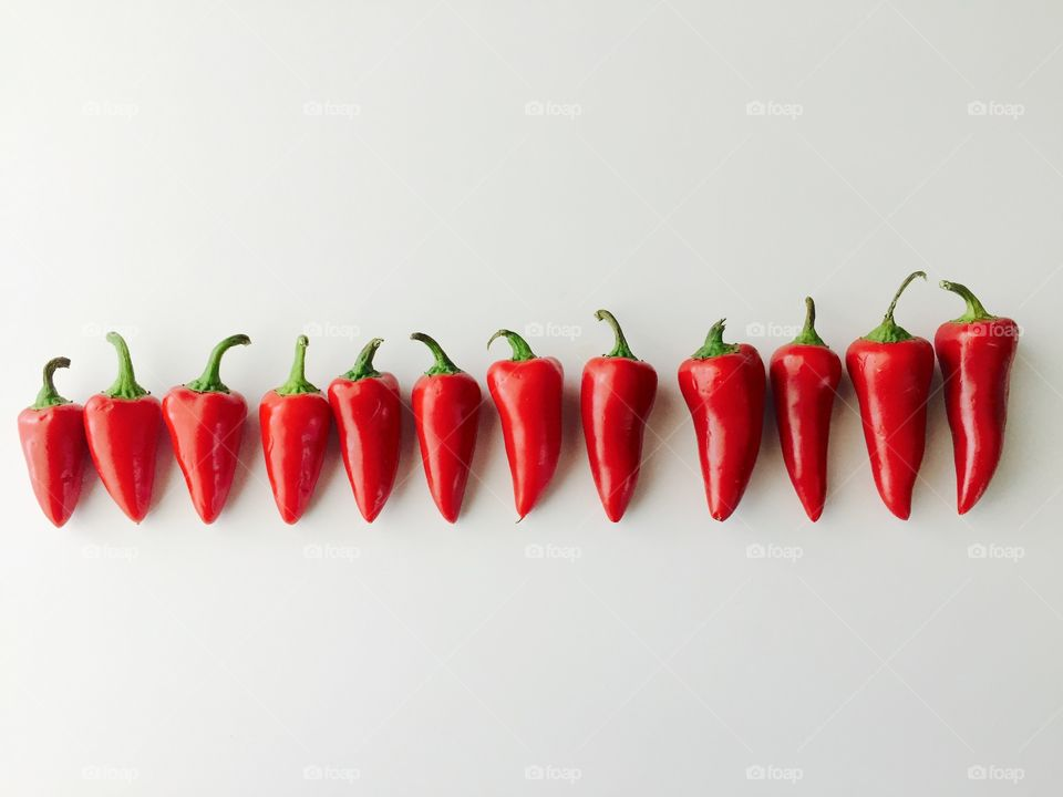 Minimalistic Snaps - Flat lay of red chili peppers, arranged horizontally by size on a white surface