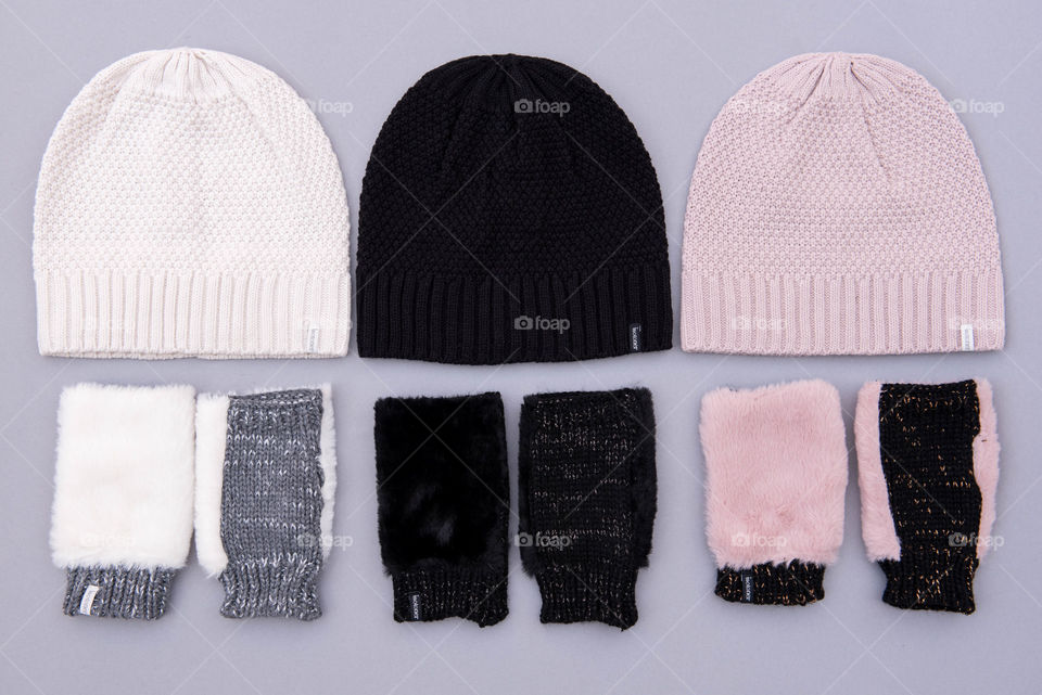 Flat lay of three sets of beanie hats and fingerless gloves
