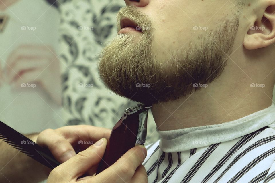 Barber shaves beard of client man on chair Barbershop. Beard Haircut. barber shaving beard with electric razor in vintage barber shop. Details of trimming. Cropped closeup of a barber trimming beard