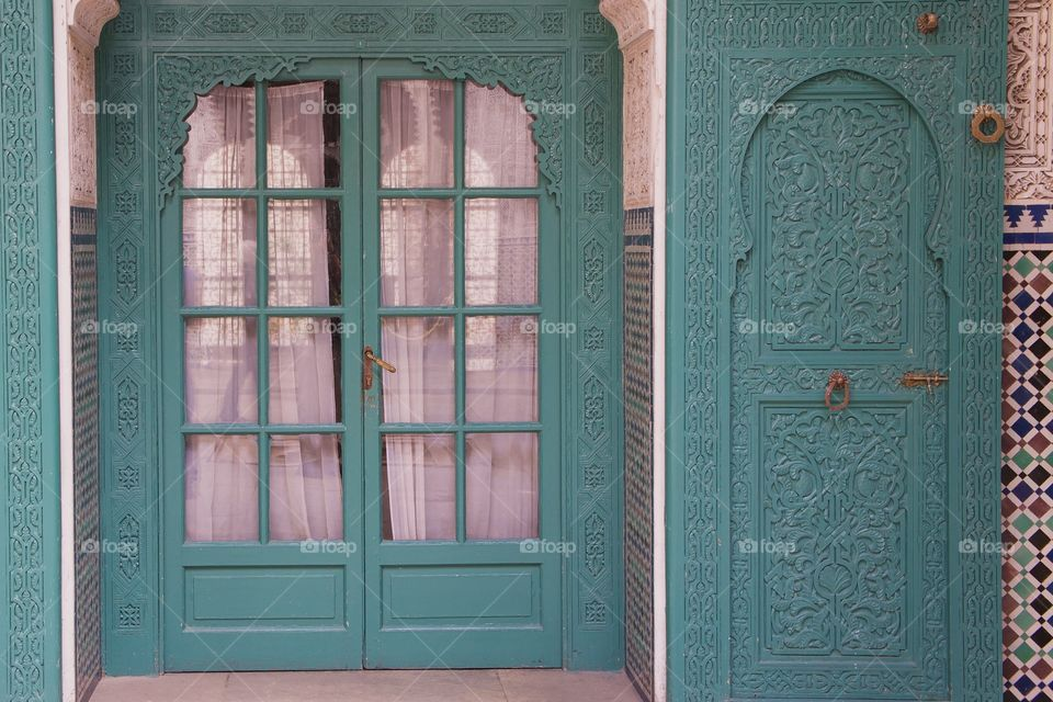 Moroccan decorative aqua wood carved doors leading from an outside court yard. In Casablanca, Morocco.