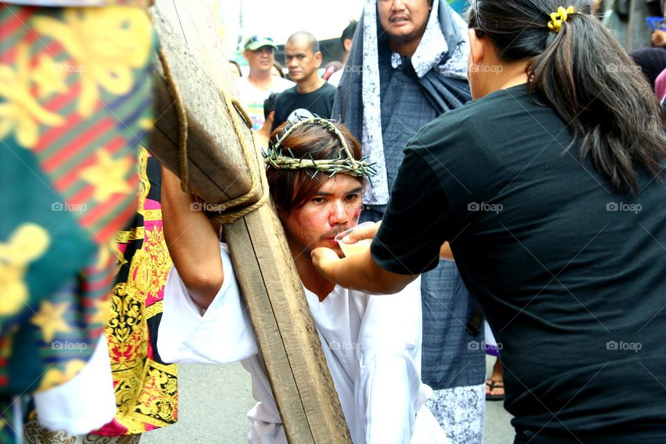 a catholic devotee is given water while reenacting the death of jesus christ on good friday during holy week in cainta, rizal, philippines, asia