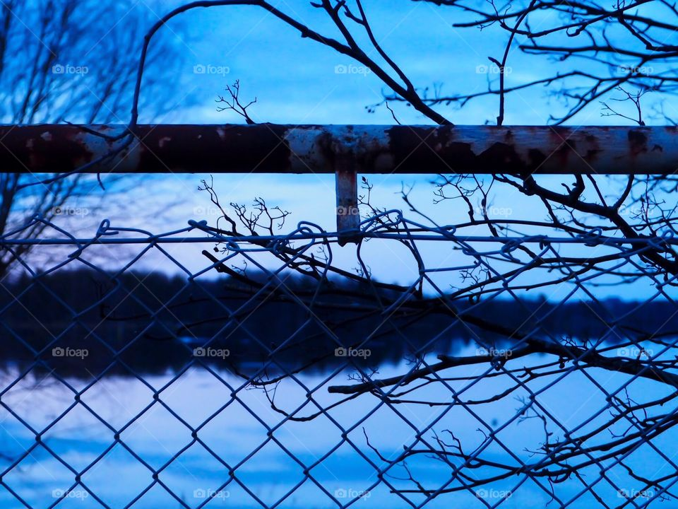 Beautiful landscape is visible through the fence. Branches and rust brings nice touch to this picture.