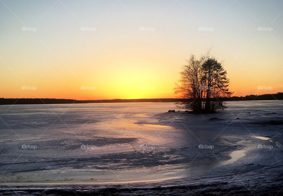 Beautiful winter sunset leaves behind wonderful colors to the sky and icy lake.
