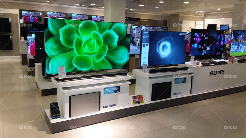 Samsung QLED television 4K Ultra High Definition TV with soundbar and sub-woofer on plinths at Peter Jones