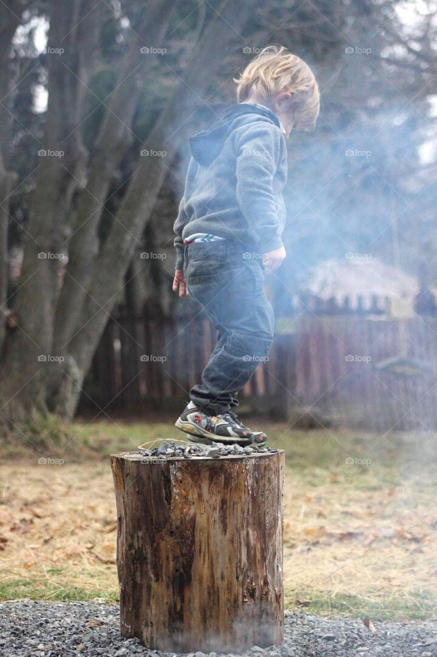 Boy standing on tree stump