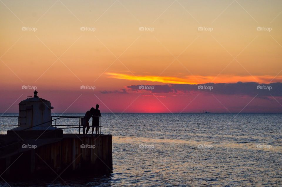 Two peoples standing on lighthouse at sunset