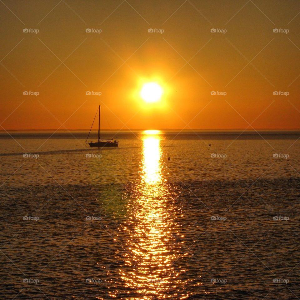 Reflection of sunlight and sailboat at sea