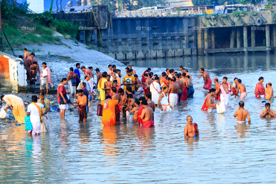 KOLKATA, INDIA - JANUARY 14, 2016: India family taking a bath on the water of Ganges during Kumbh Mela. Ganges water not even suitable for bathing, many toxic materials found: Report