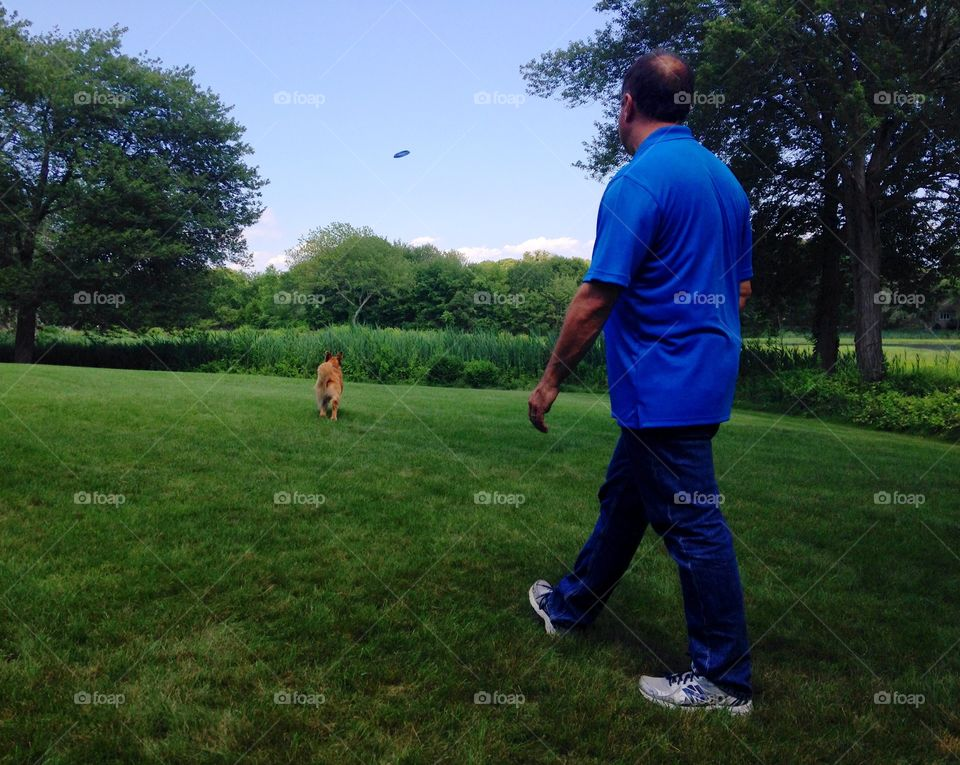 A dog and his human playing some frisbee
