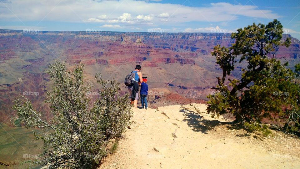 Looking over the Edge. Father and son looking over the edge of the Grand Canyon