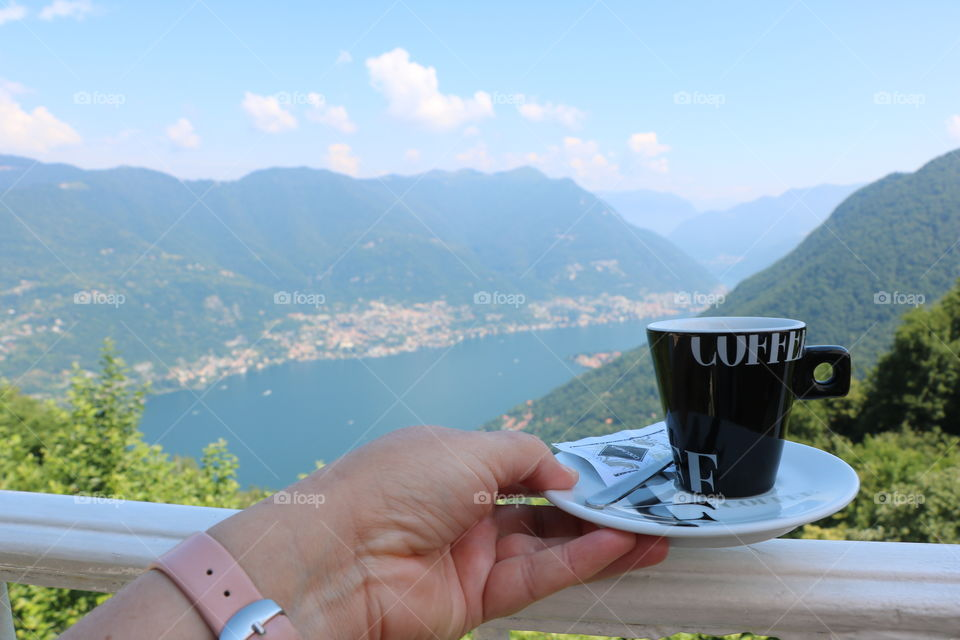 Hand holding coffee cup over the fence of a balcony overlooking the beautiful scenery of lake surrounded by mountains, on a bright summer day