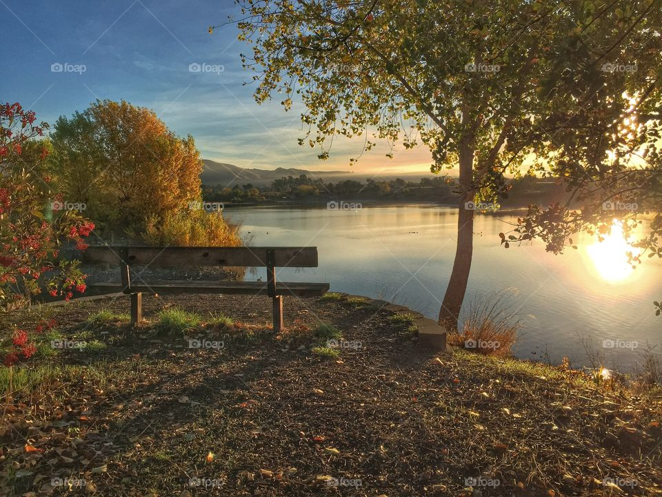 View of bench by lake during sunrise