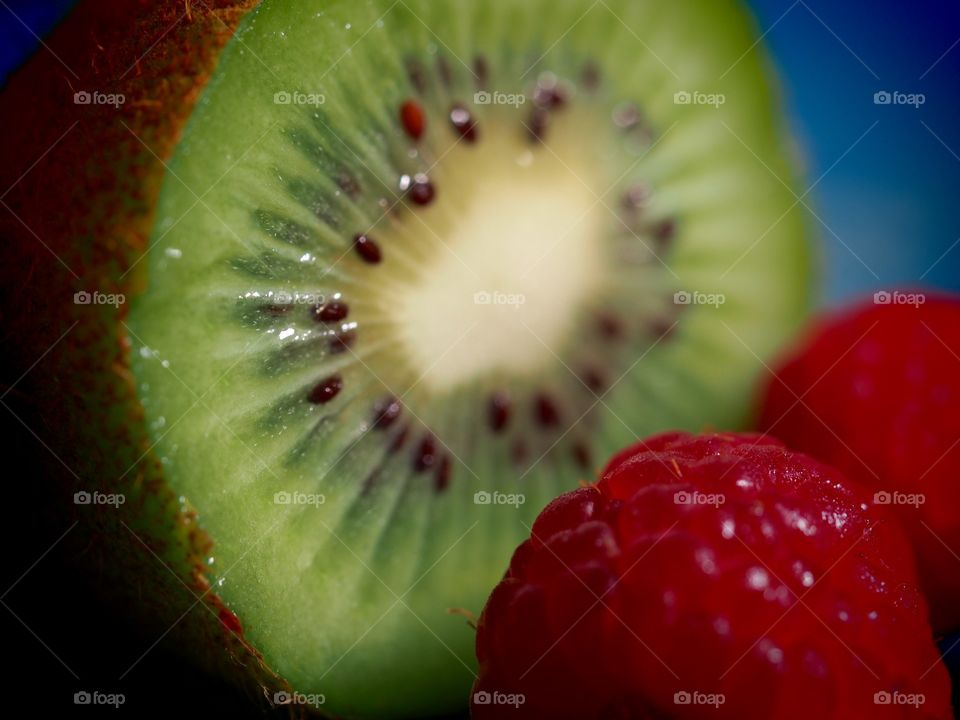 A close up of a kiwi fruit and raspberries
