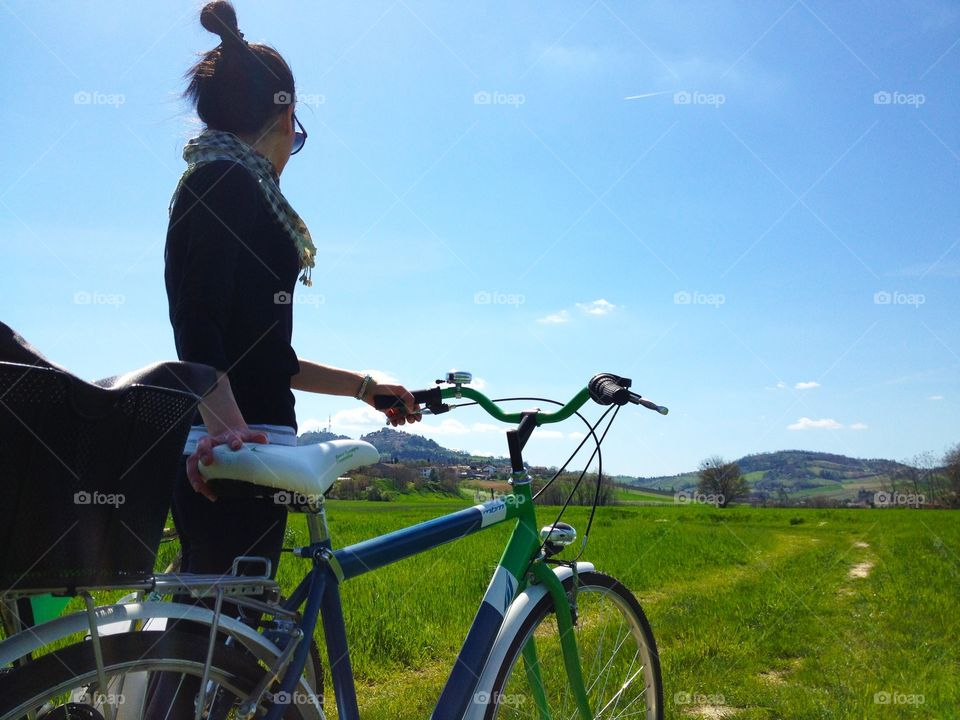 Woman and her bike in an open field. Woman and her bike in an open field