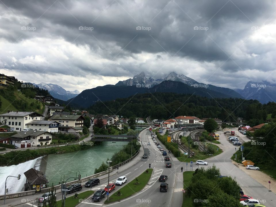 Large dark clouds loom over a small town in the German Alps, throwing shadows on a clear turquoise river, train station and road.