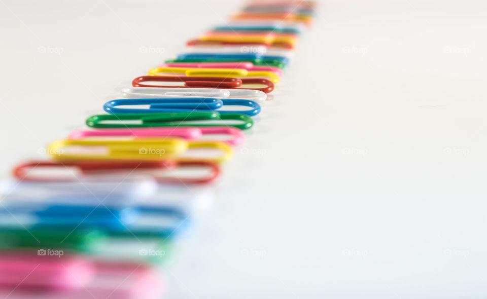 Multi coloured paper clips in white background