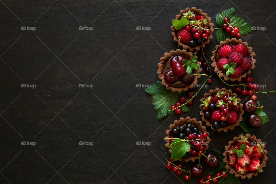 Homemade chocolate mini tarts on dark wooden background