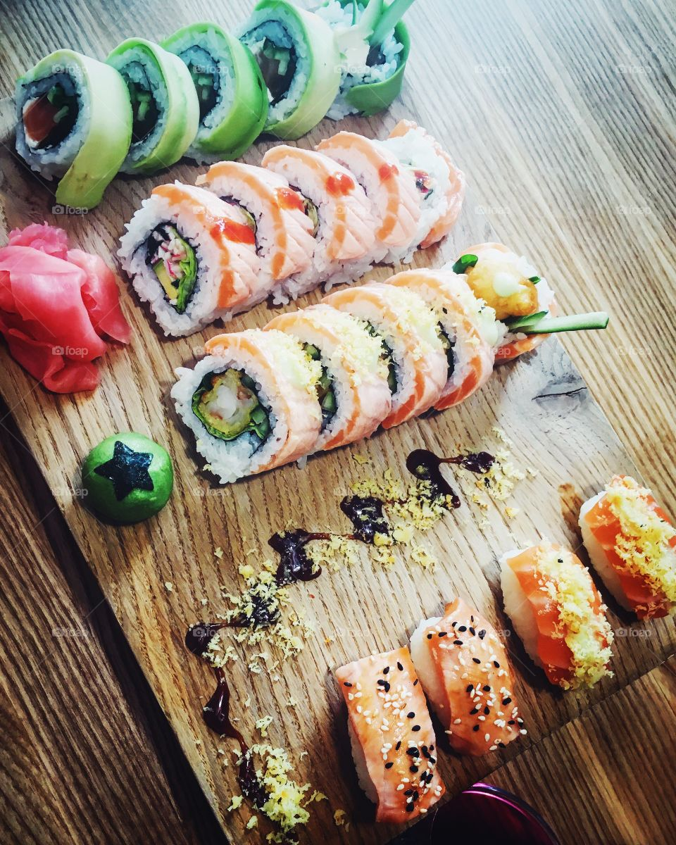 Sushi rolls on wooden table