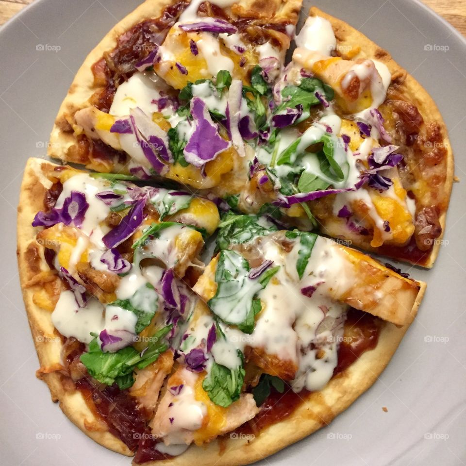 BBQ chicken pizza with creamy cheddar-mozzarella combo, caramelized onions, arugula, shredded red cabbage and ranch drizzle on top of toasted Naan flatbread