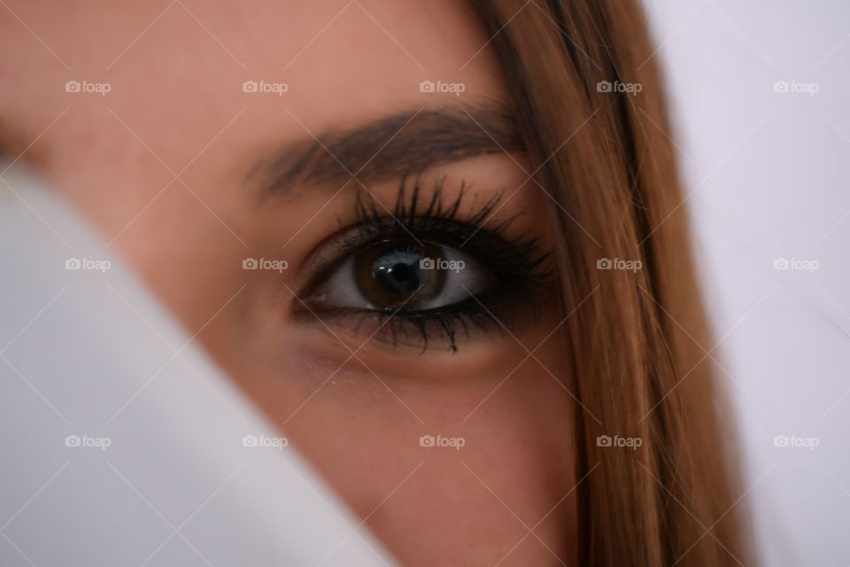 face of a woman hidden behind, eyes looking at you
