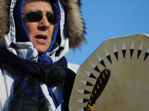 Indigenous woman playing the drum