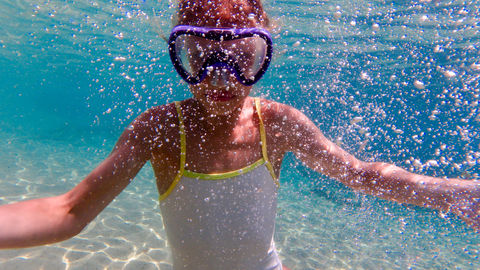 young girl diving underwater with googles in white swimsuite