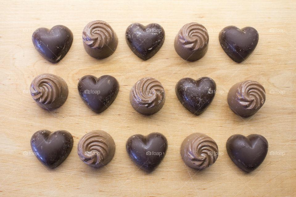 Dark chocolate hearts and milk chocolate swirls in rows on wood