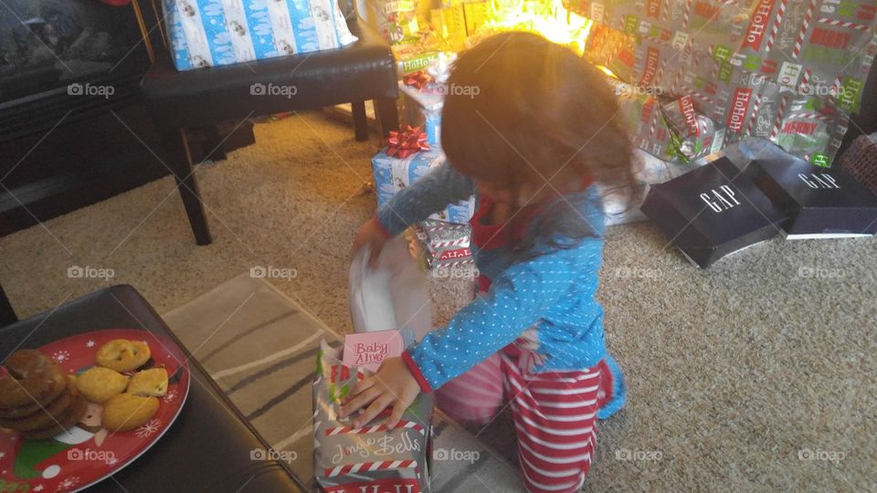 Little girl opening Christmas gifts