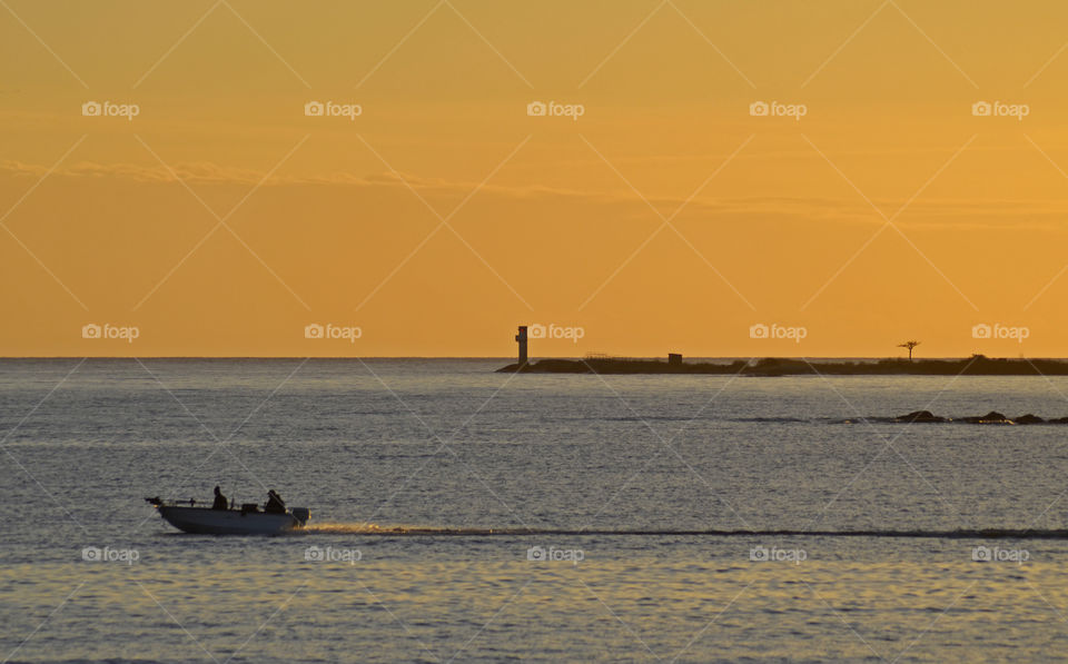 People travelling in boat at sunset