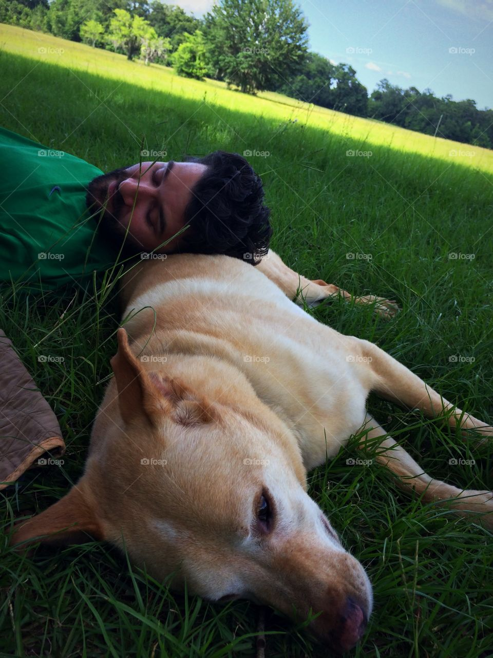 Young man sleeping with dog on grass