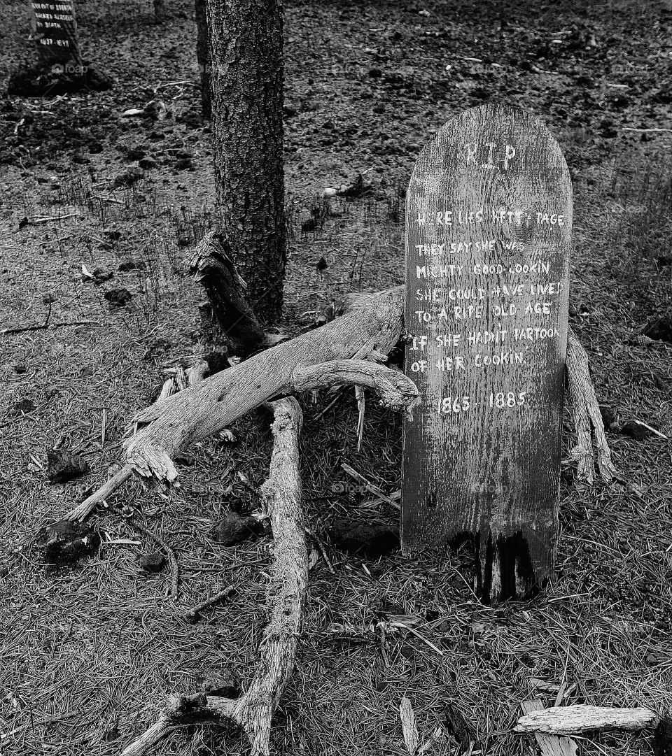 A funny wooden headstone provides a nice decoration for Halloween.