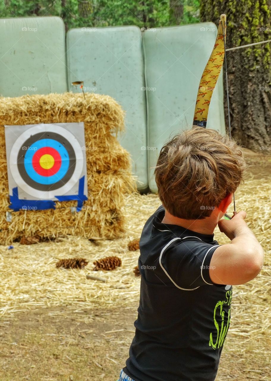 Shooting A Bow And Arrow. Boy Doing Target Practice At The Archery Range