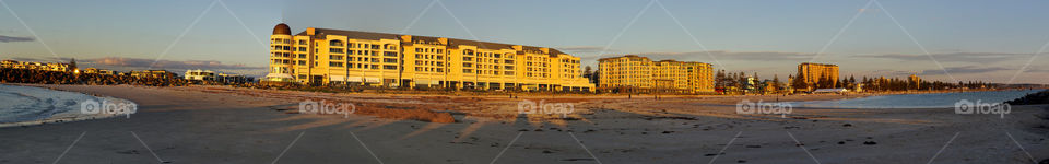 Glenelg panorama of beach. Panoramic shot if buildings at sunset and beach scenes ar Glenelg beach in Adelaide.