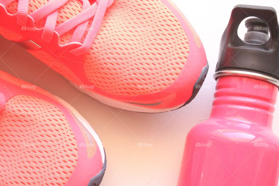 Pink sneakers and water bottle.