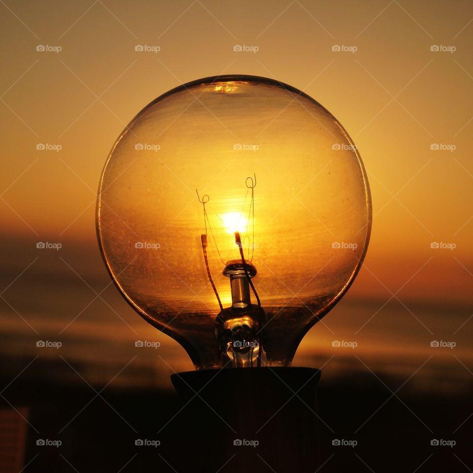 Light bulb on sunset background